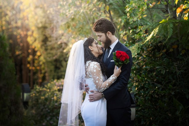 Bridal couple holding one another surrounded by greenery