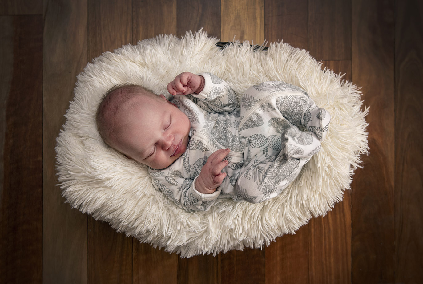 Baby in a basket on wooden floor