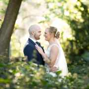 Bride and groom holding one another in the undergrowth