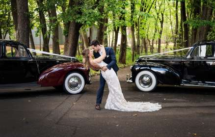 Passionate kiss in between wedding cars