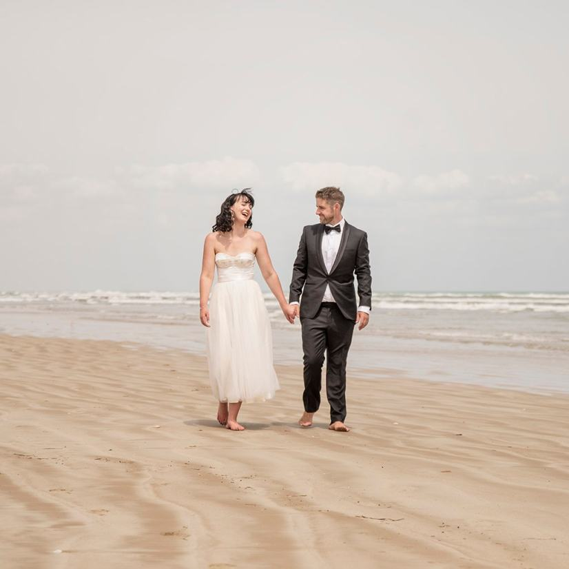 Bride and groom walking along Middleton beach