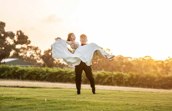 Groom lifting up bride at sunset
