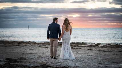 Bride and groom walking into their sunset