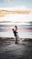 Groom lifting up bride under sunset