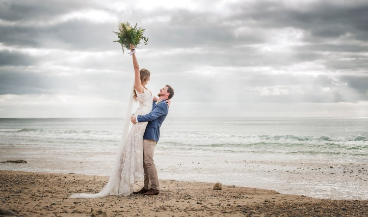 Groom lifting up his bride on beach