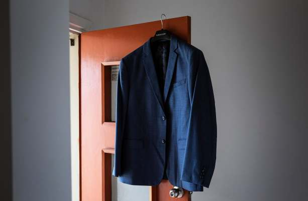 Grooms jacket hanging on door