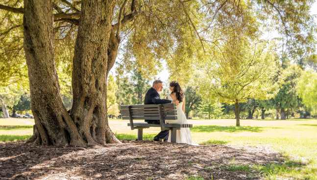 bride and groom sitting on a bench together