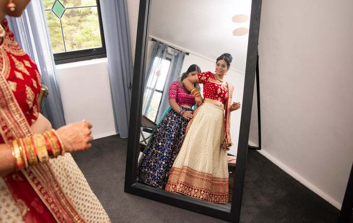Bride in Hindu garb looking in mirror