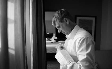 groom getting ready in black and white