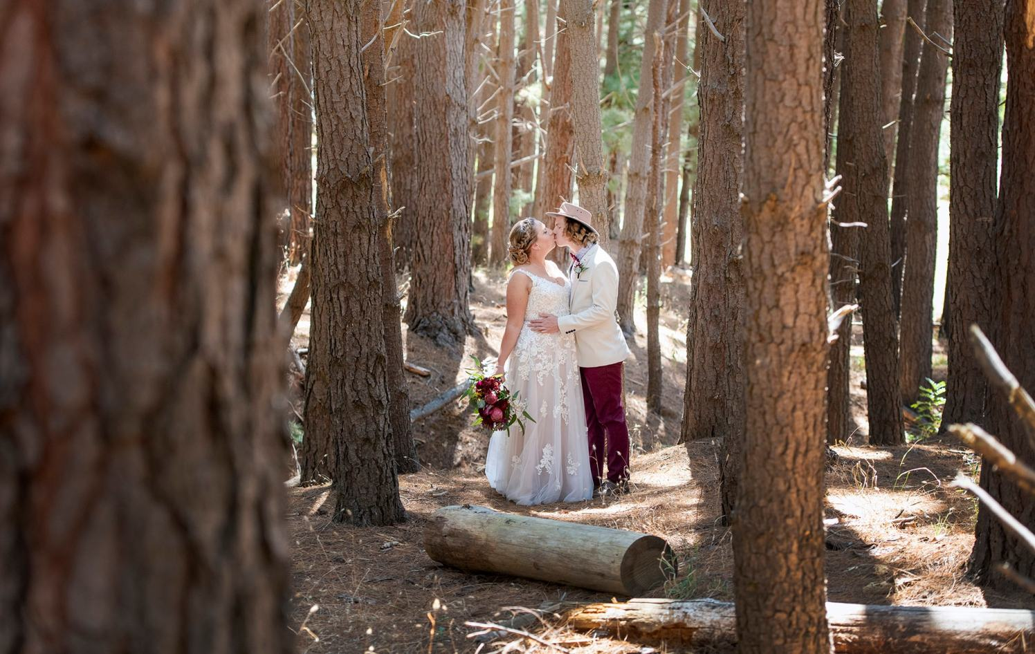 bride and groom amongst the tall pine trees