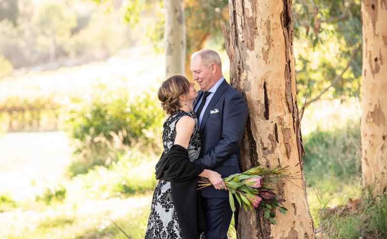 newly weds leaning against a tree