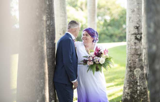 bride and groom amongst thin trees in Darwin