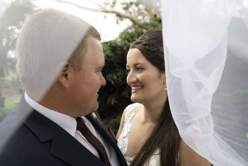 bride and groom under veil before their ceremony