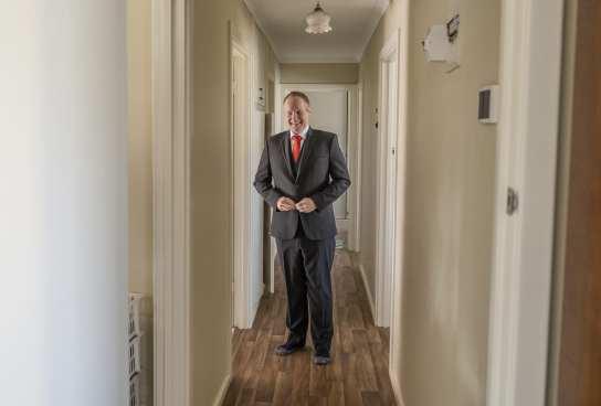 Groom standing in hallway