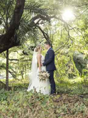 Bride and groom in green foliage
