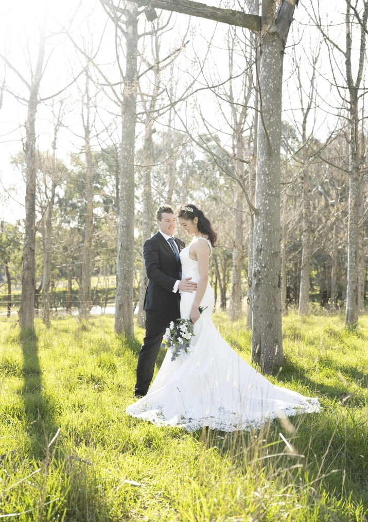 Bride and groom backdropped by sunlight