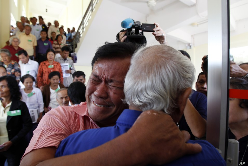 Cambodian former Khmer Rouge survivors, Soum Rithy, left, and Chum Mey, right, embrace each other after the verdicts were announced at the U.N.-backed war crimes tribunal in Phnom Penh, Cambodia, Thurdday, Aug. 7, 2014.