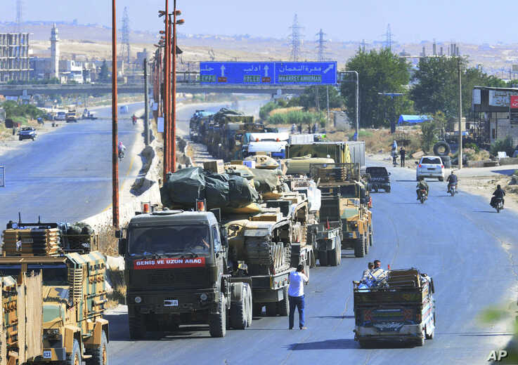 A Turkey Armed Forces convoy is seen at a highway between Maaret al-Numan and Khan Sheikhoun in Idlib province, Syria, Monday,…