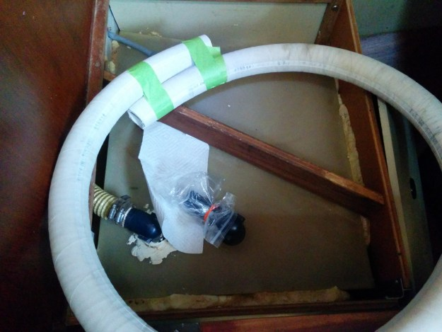 The holding tank under the nav seat, with the inlet fitting opened and a new hose lying on top.