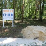 "A sign reading ""Coming 2018: CHILD Center for Early Learning"" stands next to a large dirt pile."