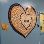 A decorative heart hanging on a wall, featuring the CHILD Center logo