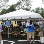 Community members celebrate the ribbon-cutting on the CHILD Center facility below a tent canopy.