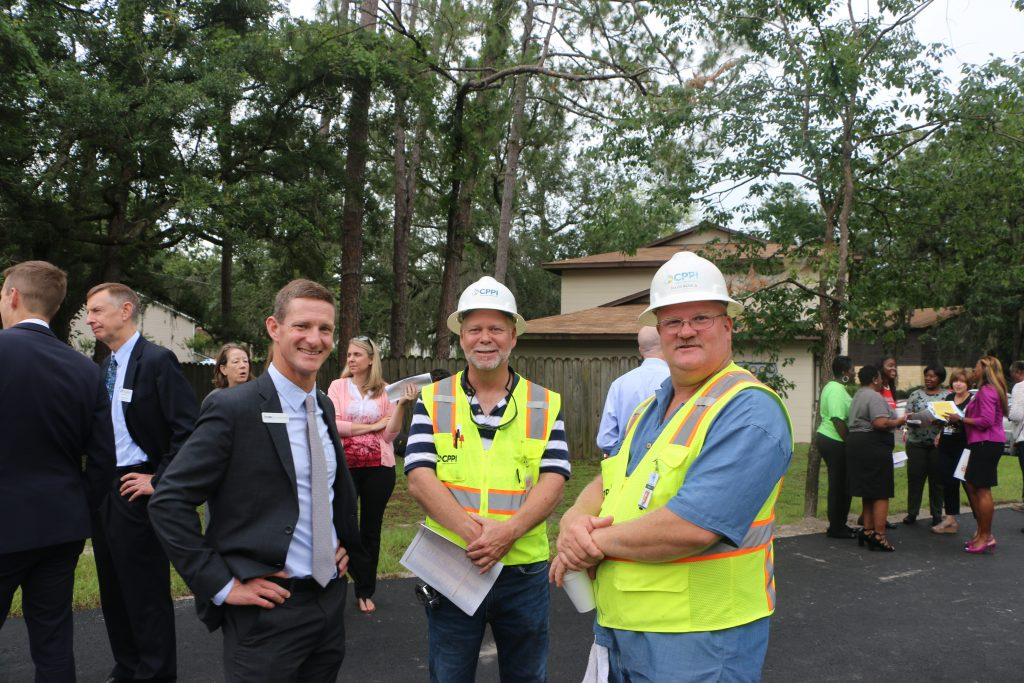 Two men in construction uniforms and one man in a business suit smile for the camera.