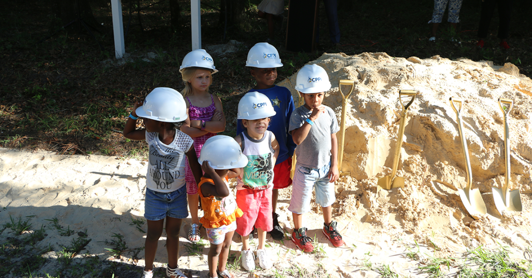"Six children wearing construction hats stand next to a large mound of dirt and a ""Coming Soon"" sign for the CHILD Center."