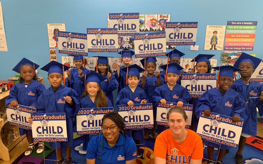 The CHILD Center class of 2020 wears blue regalia and holds signs announcing their graduation