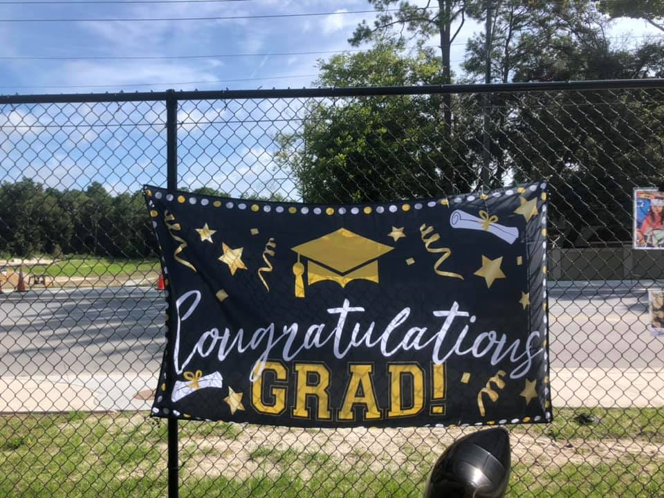"A hanging sign that reads, ""Congratulations Grad!"""