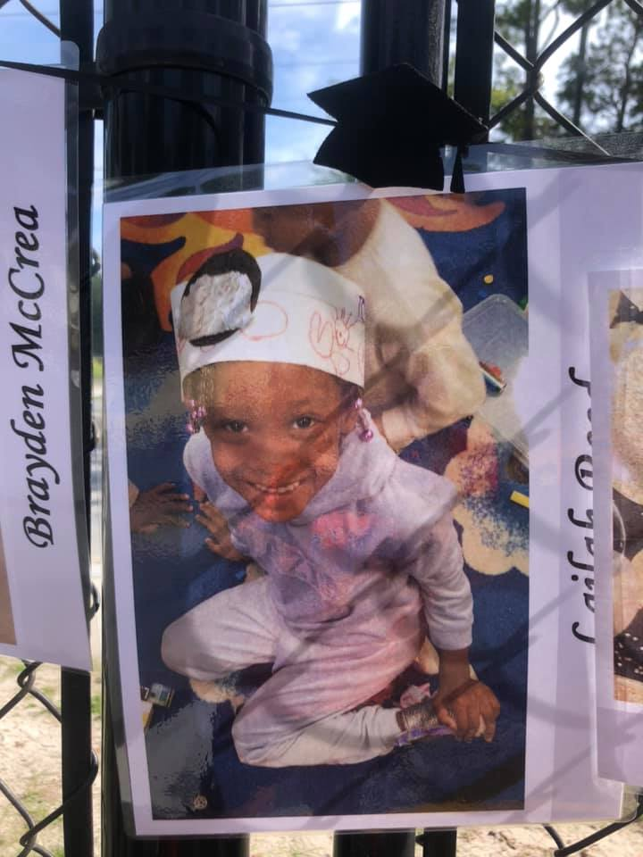 A photo of a 2020 CHILD Center graduate in displayed on the CHILD Center fence
