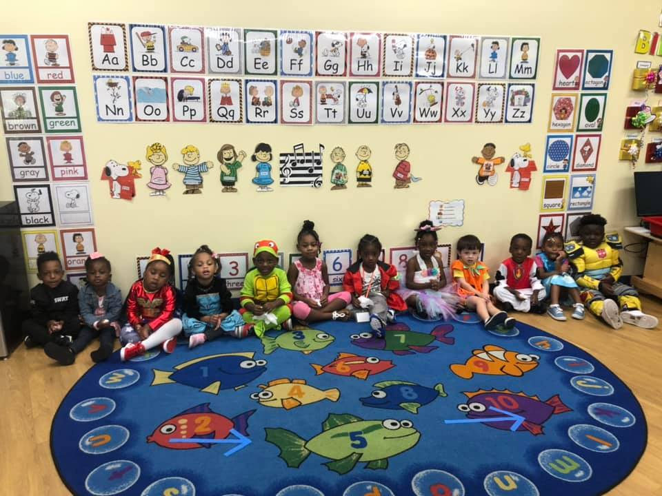 CHILD Center students sitting a line on the classroom rug
