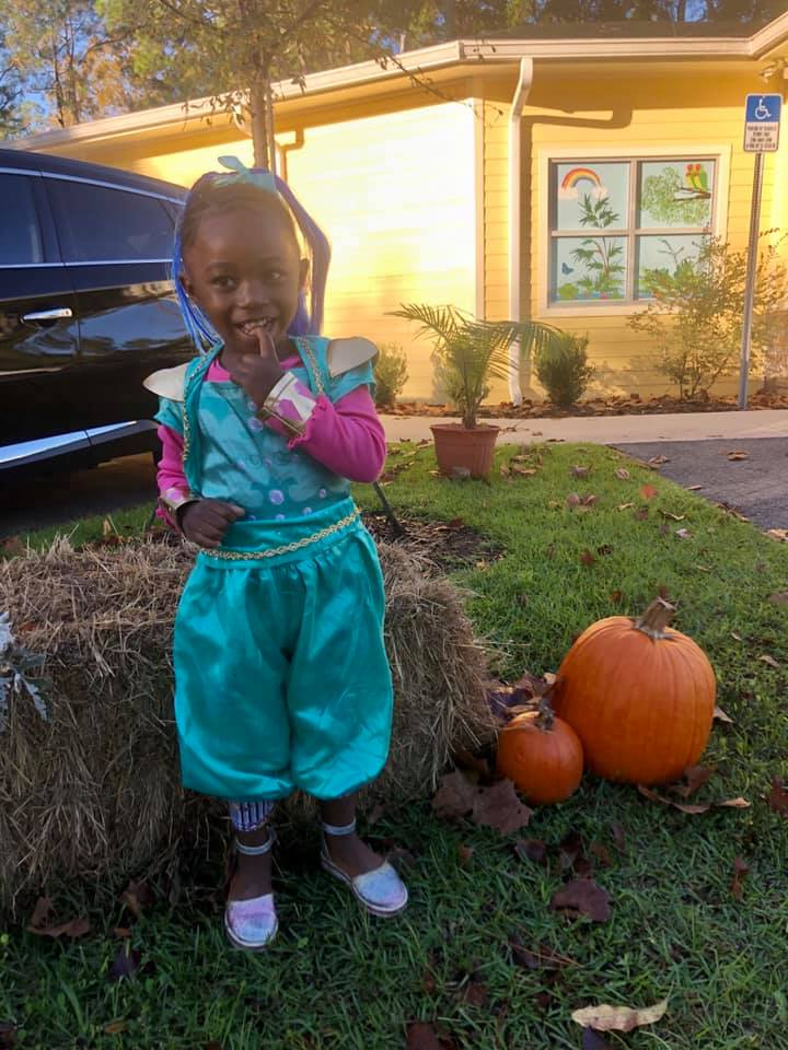 A CHILD Center student wearing a Halloween costume and standing next to pumpkins outside the CHILD Center