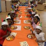 CHILD Center students sit together at a long table for a Thanksgiving feast