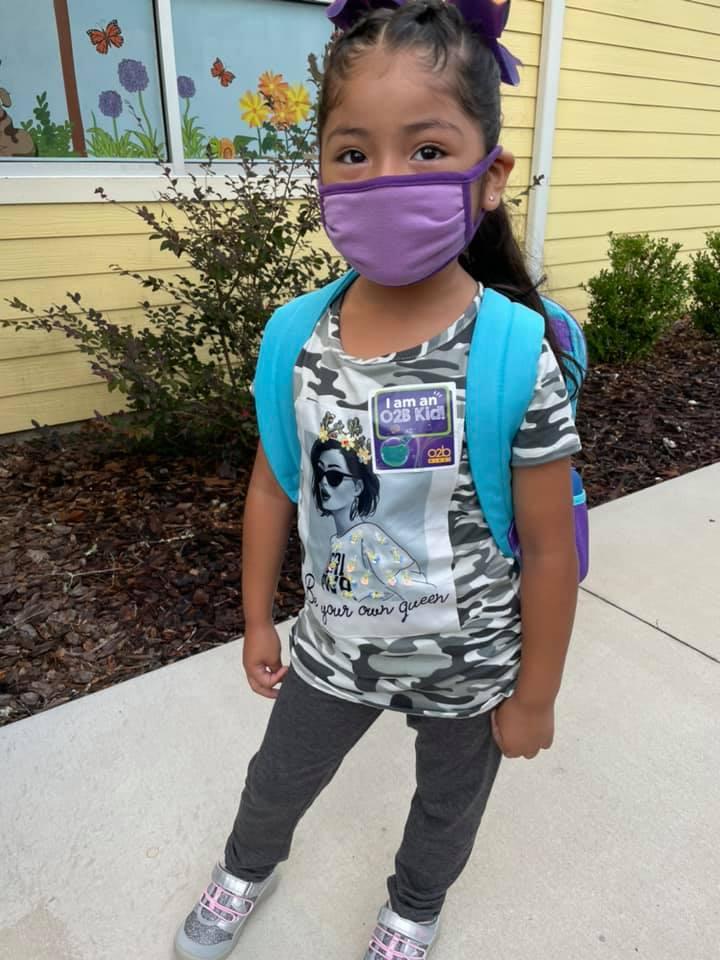 A child wears a mask and a backpack, ready for a new school year after Summer 2021