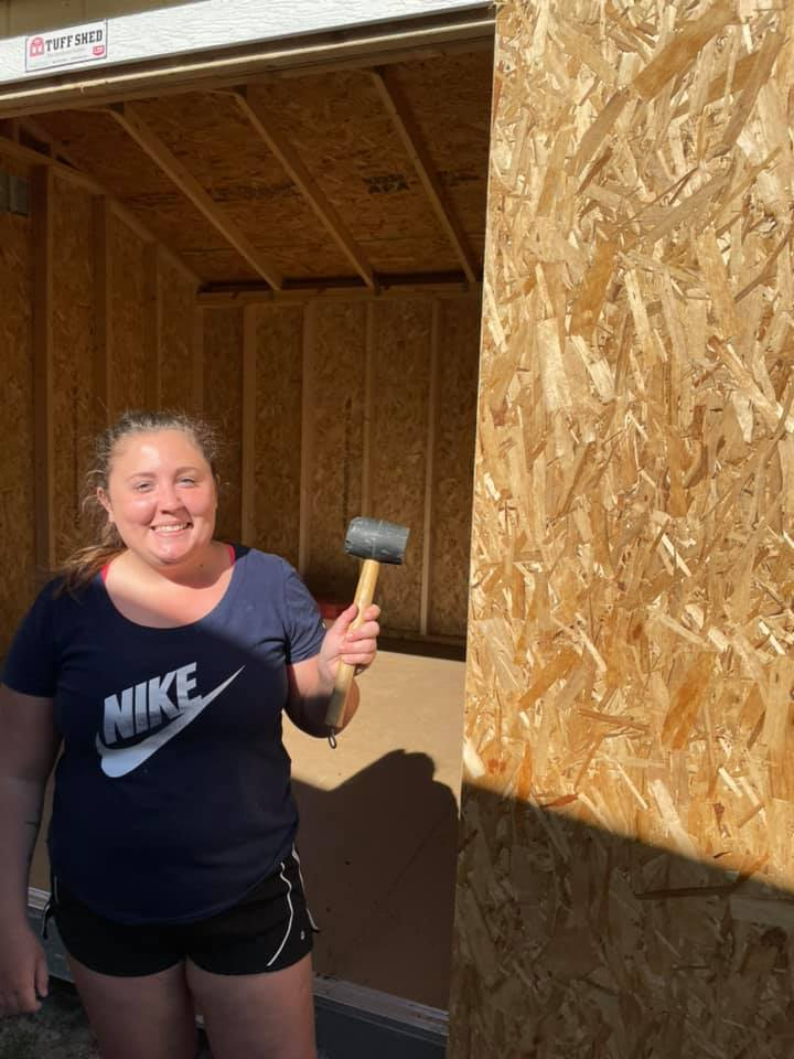 A volunteer holds a rubber hammer in front of the storage shed at the CHILD Center