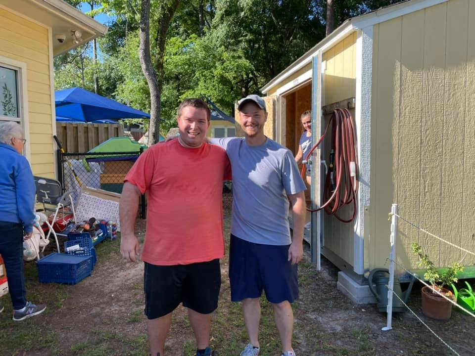 Two Gainesville Rotary Club volunteers stand together behind the CHILD Center on fence-building day in Summer 2021