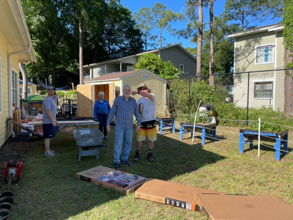 Volunteers work together to install a new white fence behind the CHILD Center
