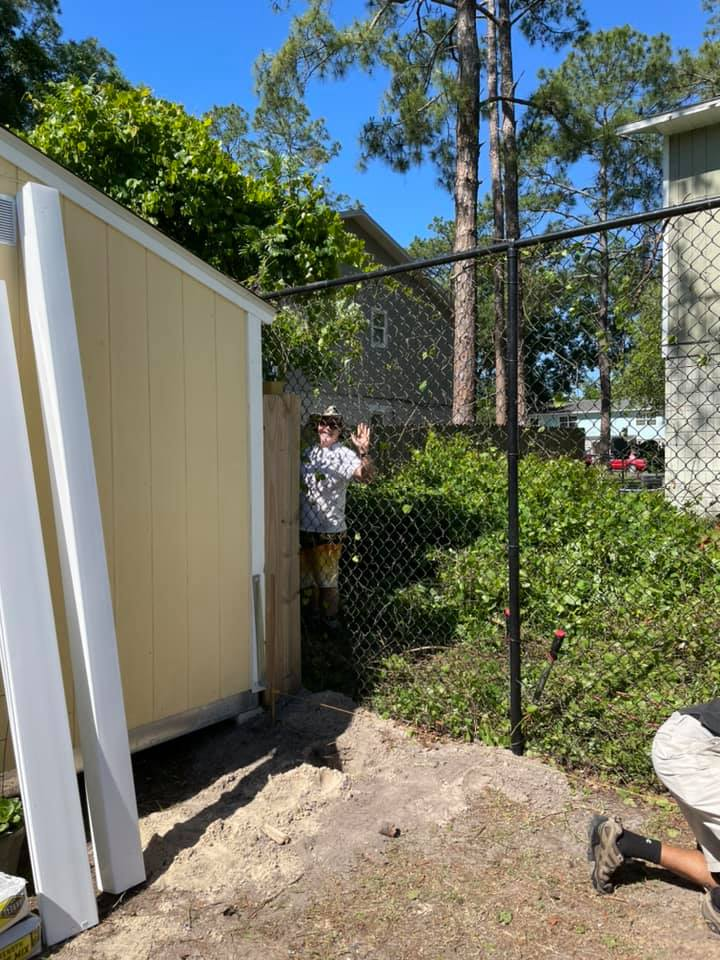 A volunteer prepares the space where a new fence will be erected behind the CHILD Center