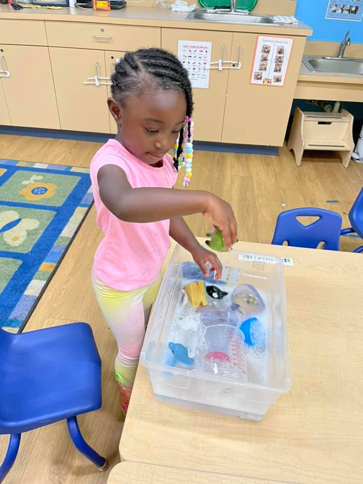 A young girl plays with toys floating in a bin of water at the CHILD Center