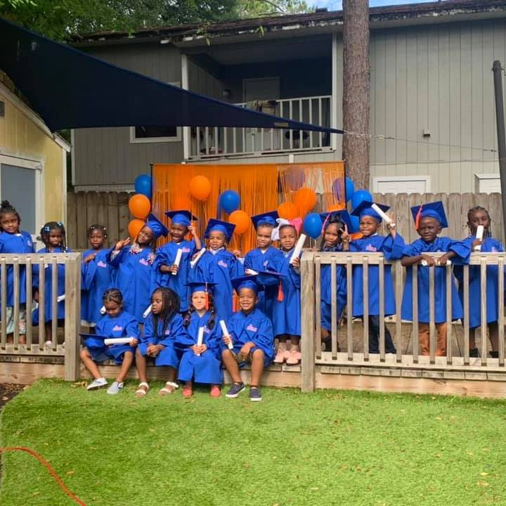 The Summer 2021 graduates pose in a large group in blue caps and gowns.
