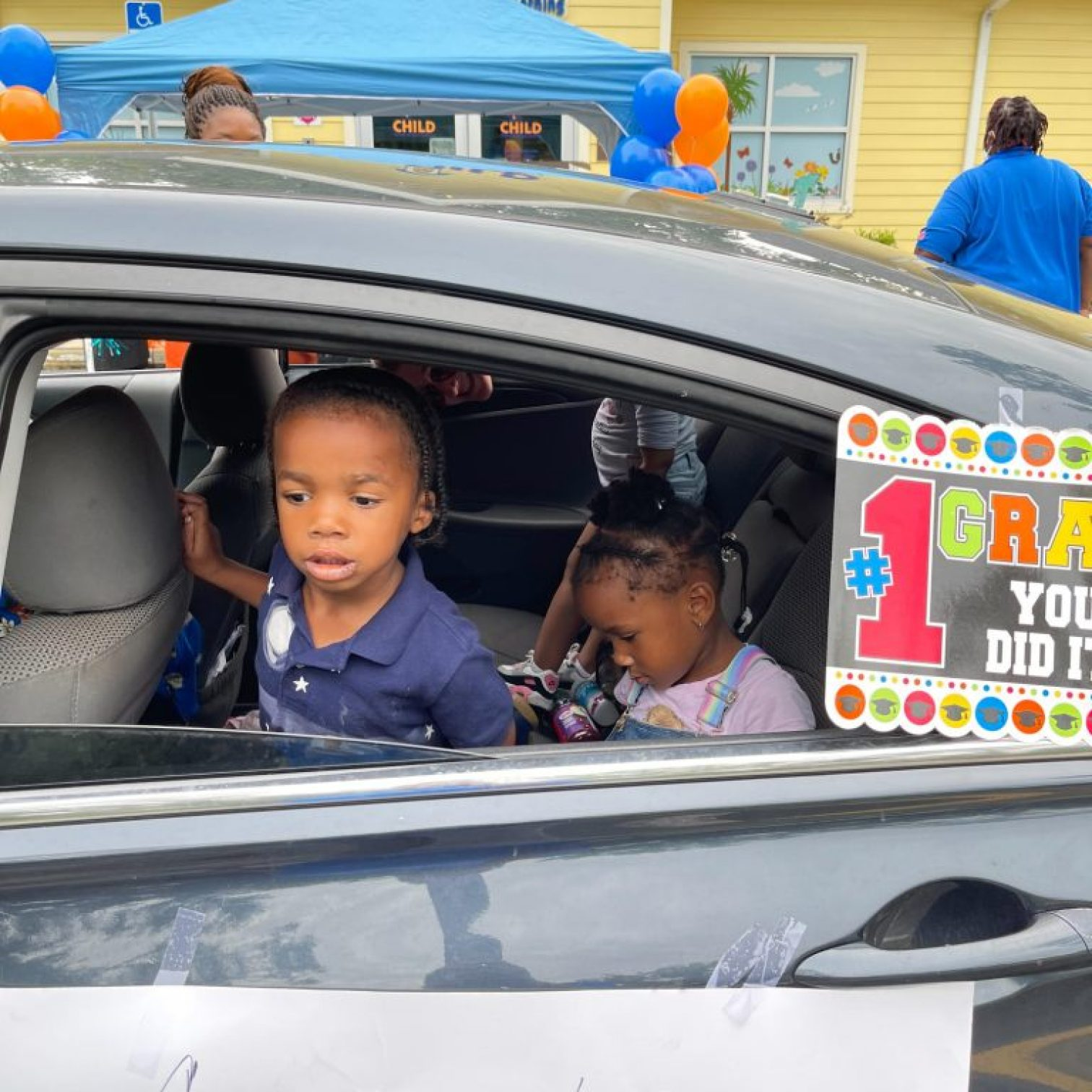 """Two young children ride in the back of a car decorated with a sign that reads, """"#1 GRAD, YOU DID IT!"""""""