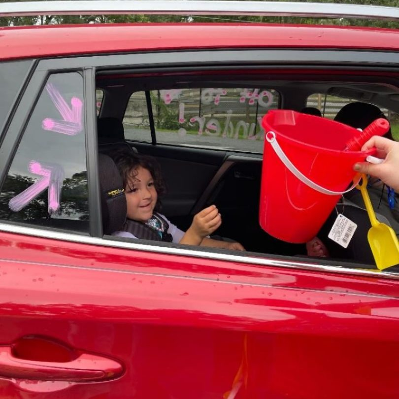 """A young child receives a graduation gift through the window of a car during the Summer 2021 """"Buzz-By"""" graduation"""