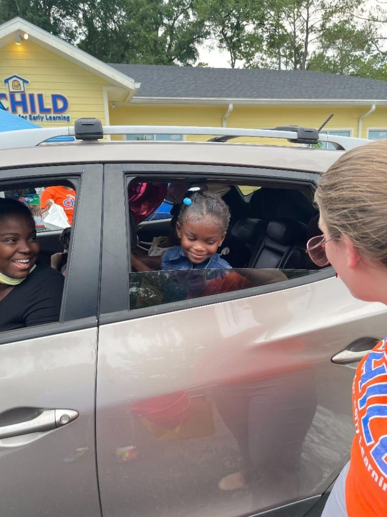 A small child smiles out the window of a car at a CHILD Center staff member, and the grown-up driver looks back at her smiling