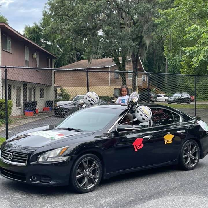 """A car decorated with """"Congrats Grad"""" balloons rolls by the CHILD Center during the 2021 """"Buzz-By"""" graduation celebration"""