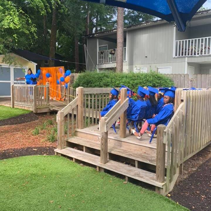 The Summer 2021 CHILD Center graduates sit in chairs arranged on the back deck of the Center for the graduation ceremony
