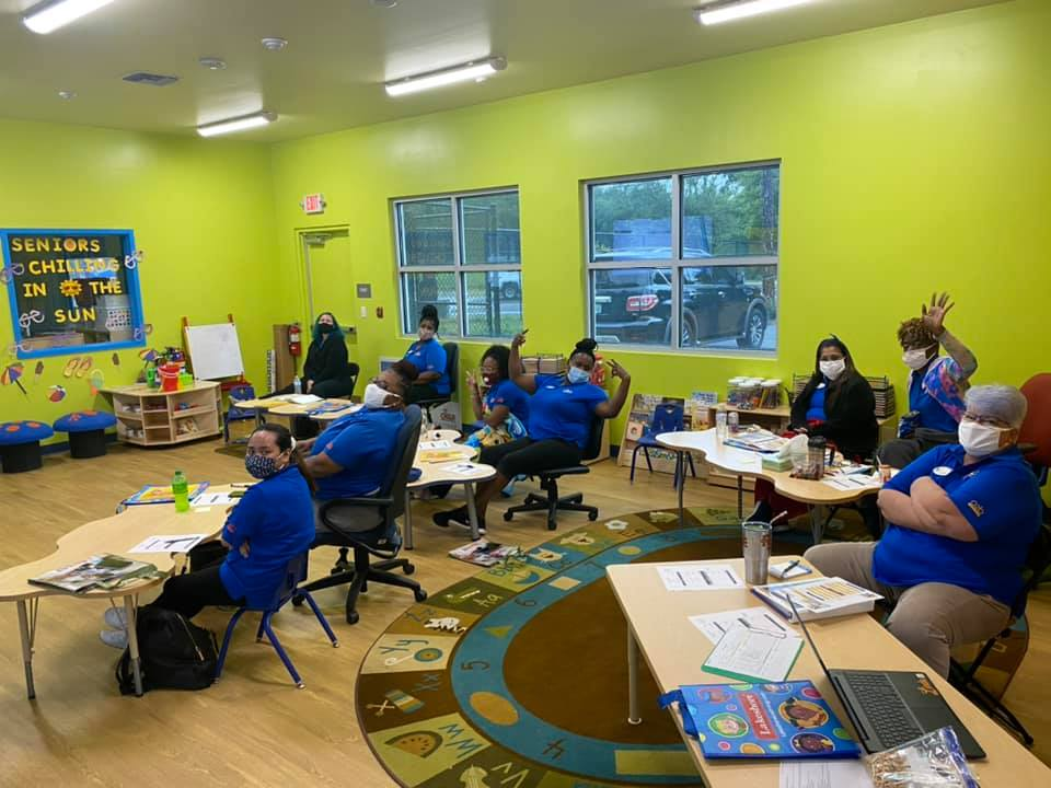CHILD Center staff all wear blue tee shirts and sit around tables for their Summer 2021 training