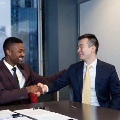 Ray J and Ray Lee of Cowboy Wholesale shake hands after signing the paperwork cementing their $31 million Raycon distribution deal.