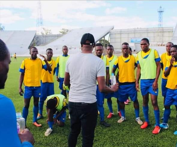 Hangover United FC players listening to their coach in a practice