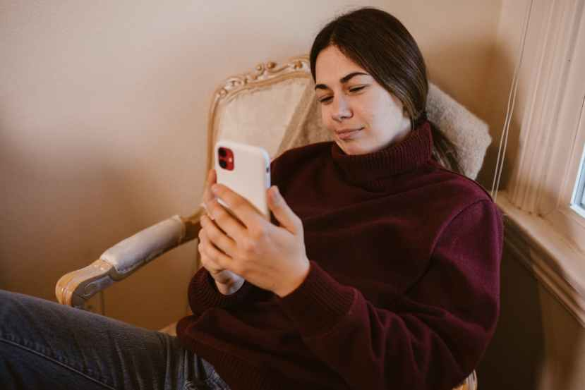 woman in maroon sweater holding white smartphone